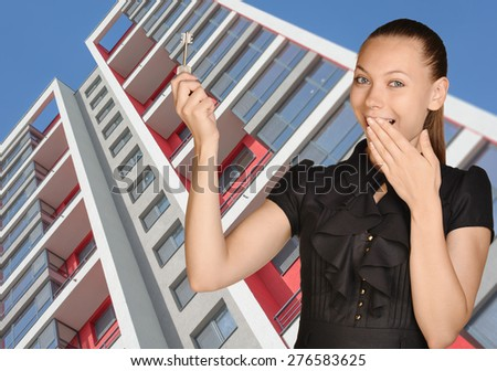 Successful girl standing on background of building and is holding keys. - stock photo