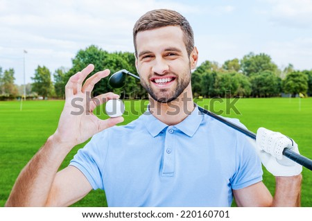 Successful golfer. Happy young man holding golf ball and driver while standing on green - stock photo