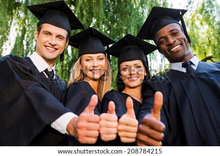 Successful graduates. Low angle view of four college graduates in graduation gowns standing close to each other and showing their thumbs up - stock photo