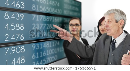 Successful group of businesspeople headed by senior manager analyzing stock market on large digital display