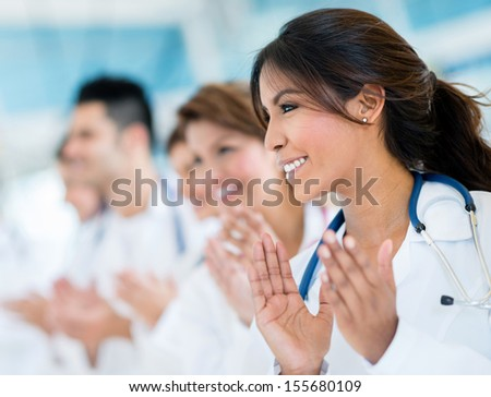 Successful group of doctors applauding at the hospital  - stock photo