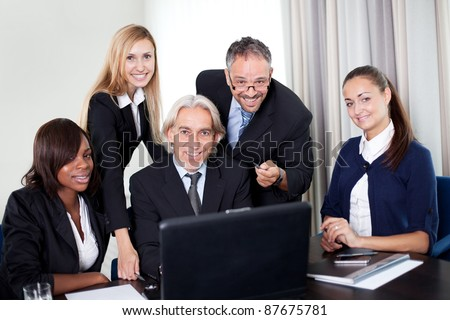 Successful group of mature entrepreneur in a meeting at the office with laptop - Smiling at the camera - stock photo