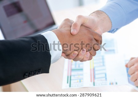 Successful handshake. Two Confident businessman sitting at the negotiating table in the office and shaking hands close-up view of hands. Business people dressed in formal wear - stock photo