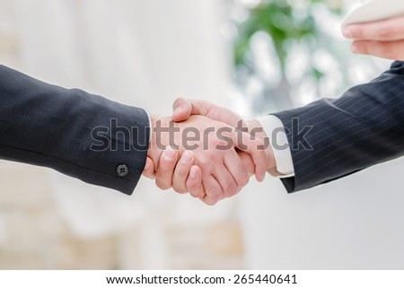 Successful handshake. Two successful businessman standing in the restaurant and drink coffee while shaking hands with each other close-up view of hands