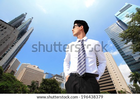 Successful handsome business man purposefully looking away with blue sky in the city, asia, china, hong kong - stock photo