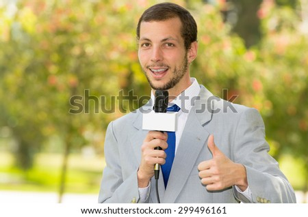 Successful handsome male news reporter in light grey suit working outdoors in park environment holding microphone in live broadcasting. - stock photo