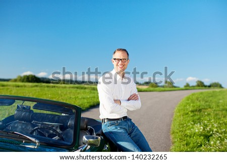 Successful handsome man relaxing leaning on a cabriolet car parked in a rural road running through a green field under a sunny blue sky