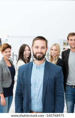 Successful handsome young bearded business manager posing in front of his team of colleagues smiling at the camera - stock photo