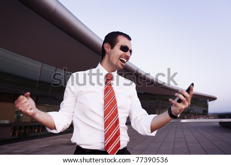 Successful happy businessman in white shirt and sunglasses cheering as having received good news on cell phone with office building in background. - stock photo