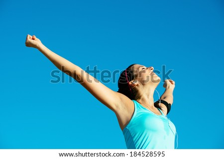 Successful happy fitness woman raising arms to the sky after sport achievement outdoor. Sporty girl enjoying freedom. - stock photo