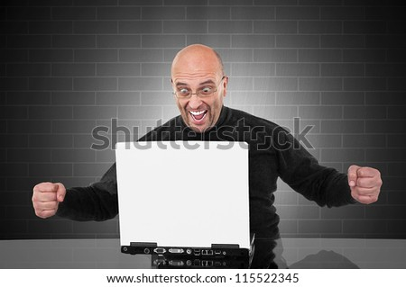 Successful happy man in front of his laptop with space for your text - stock photo