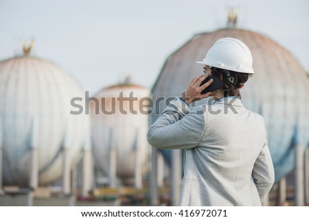 successful independent engineer woman talking on the phone on industrial area with safety helmet showing back. Pioneer woman at work with spherical tanks. - stock photo