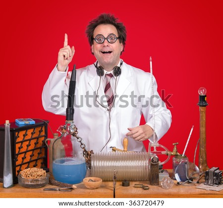 successful inventor at his desk with equipment on red background. Genius professor shows triumph for invention. Successful scientific research. The inventor of celebrating success in the lab. - stock photo