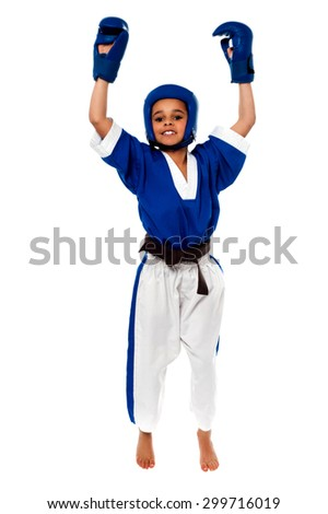 Successful karate kid with raised arms over white - stock photo