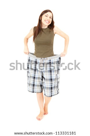 successful losing weight, girl in big trausers, full length, white background - stock photo