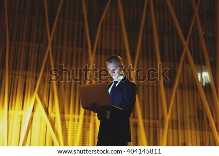 Successful male banker using laptop outdoors while standing near his office, young professional manager working working on his notebook computer near skyscraper at night - stock photo