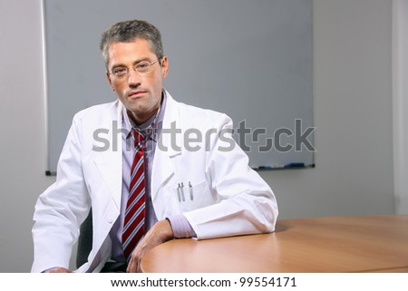 Successful male doctor sitting in the office - stock photo