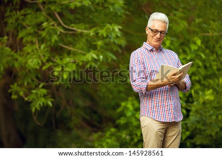 Successful man concept. Portrait of a smiling happy mature (old) man in trendy casual shirt & glasses looking at something and reading book in the park. Sunny summer day. Copy-space. Outdoor shot - stock photo