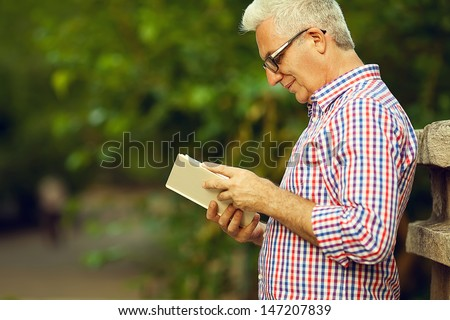 Successful man concept. Profile portrait of a smiling happy mature (old) man in trendy casual shirt & glasses reading book in the park. Sunny summer day. Copy-space. Outdoor shot - stock photo