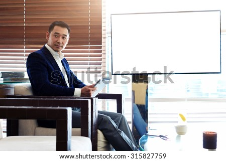 Successful man in elegant suit using digital tablet during preparation for the business meeting, confident asian male working on touch pad while sitting in cafe near empty blank screen with copy space - stock photo