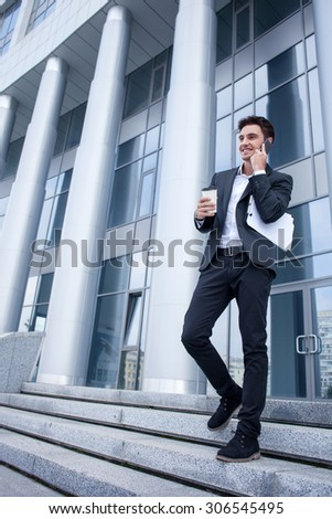 Successful man in suit is moving on steps outdoors. He is talking on the phone and smiling. The man is holding documents and a cup of coffee. Copy space in left side