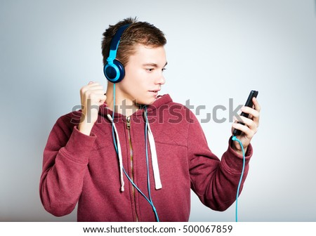 successful man listening to music with beautiful headphones isolated on a gray background