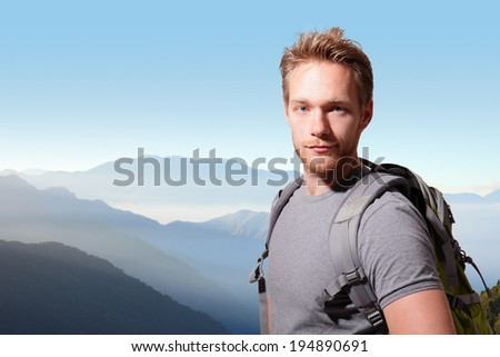 Successful man mountain hiker with backpack on the top of mountains. caucasian - stock photo