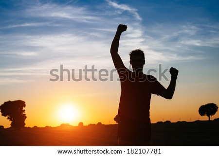 Successful man raising arms after cross country running on summer at sunset. Male athlete with arms up celebrating success and sport goals after exercising and working out. - stock photo
