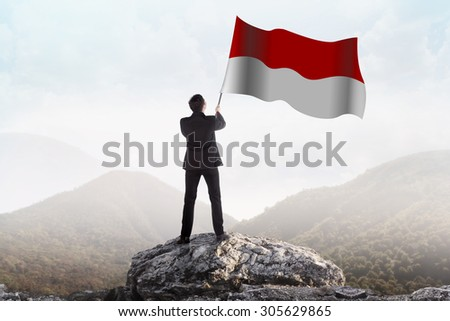 Successful man waving Indonesian flag on top of the mountain peak - stock photo