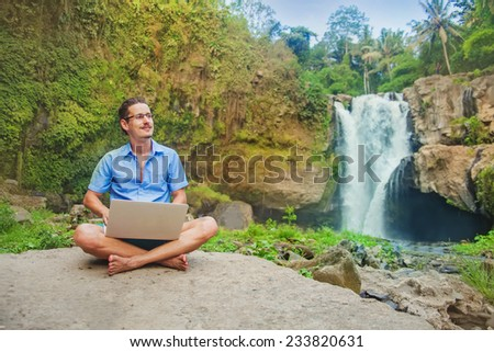 successful man with laptop in a jungle