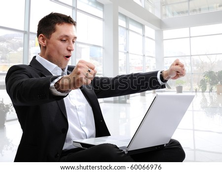 successful man with laptop in modern white office with glass around - stock photo