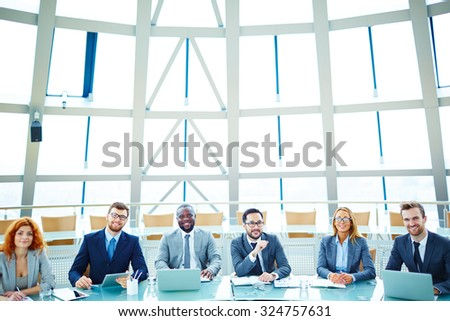 Successful managers sitting in conference hall and looking at camera - stock photo