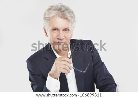Successful mature businessman looking at camera  at work in office