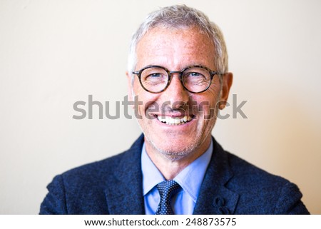 Successful mature handsome businessman smiling wearing a pair of glasses - stock photo