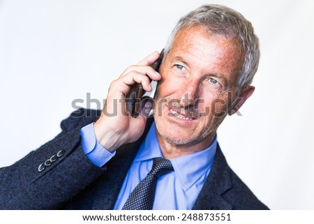Successful mature handsome businessman using his smart phone for a job call. Communictaion and technology theme - stock photo