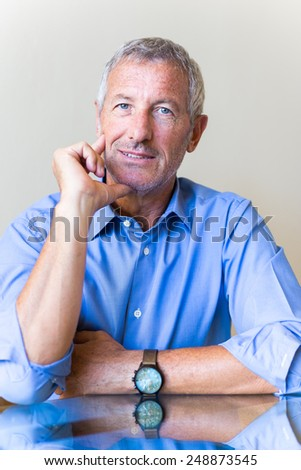 Successful mature handsome businessman waiting for you for an interview - stock photo
