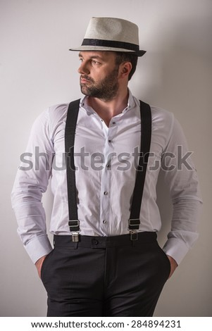 Successful mature man in formal wear looking away on grey background. Studio shot.