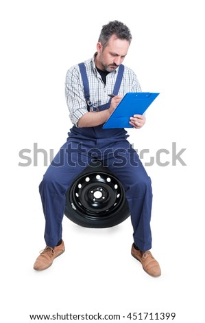 Successful mechanic sitting on wheel and writing on checklist about auto repairing isolated on white background - stock photo
