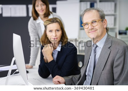 Successful middle-aged business team working together around a desktop computer with focus to an attractive manageress in the centre