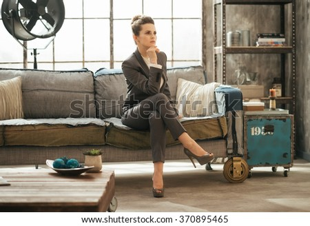 Successful modern business woman freshen up before work in her perfect loft apartment. Elegant brunet business woman is sitting on couch - stock photo