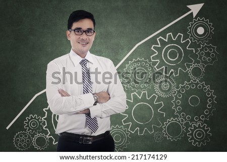 Successful modern businessman and financial graph, gear, on the wall