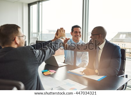 Successful multiethnic business team congratulating each other on an achievement giving a high fives gesture with their hands - stock photo