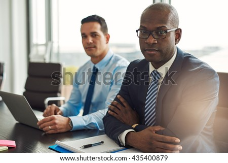 Successful multiracial business partners in a meeting together with a young Hispanic man using a laptop and African American man sitting with folded arms looking at the camera - stock photo