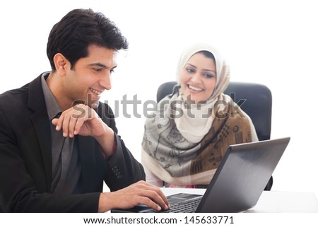 successful muslim business woman in a meeting with her caucasian male colleague; young business couple in an official meeting. business couple working on the laptop - stock photo