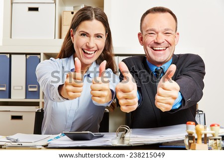 Successful office business team holding their thumbs up and smiling - stock photo