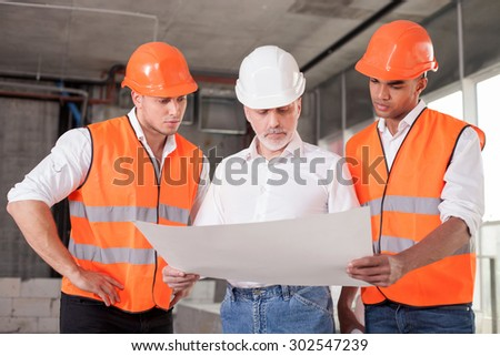 Successful old architect and two workers are discussing the plan of building. They are looking at the blueprint with seriousness - stock photo