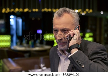 Successful old businessperson is talking on telephone - stock photo