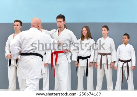 successful old karate master trains a group of young people karate - stock photo