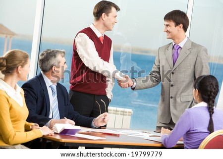 Successful partners shaking hands while their colleagues looking at them - stock photo