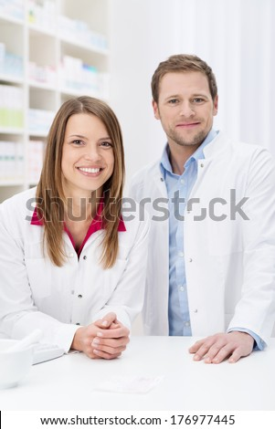 Successful pharmacy partnership with a confident young male and female pharmacist standing close together behind the counter in the pharmacy smiling at the camera - stock photo